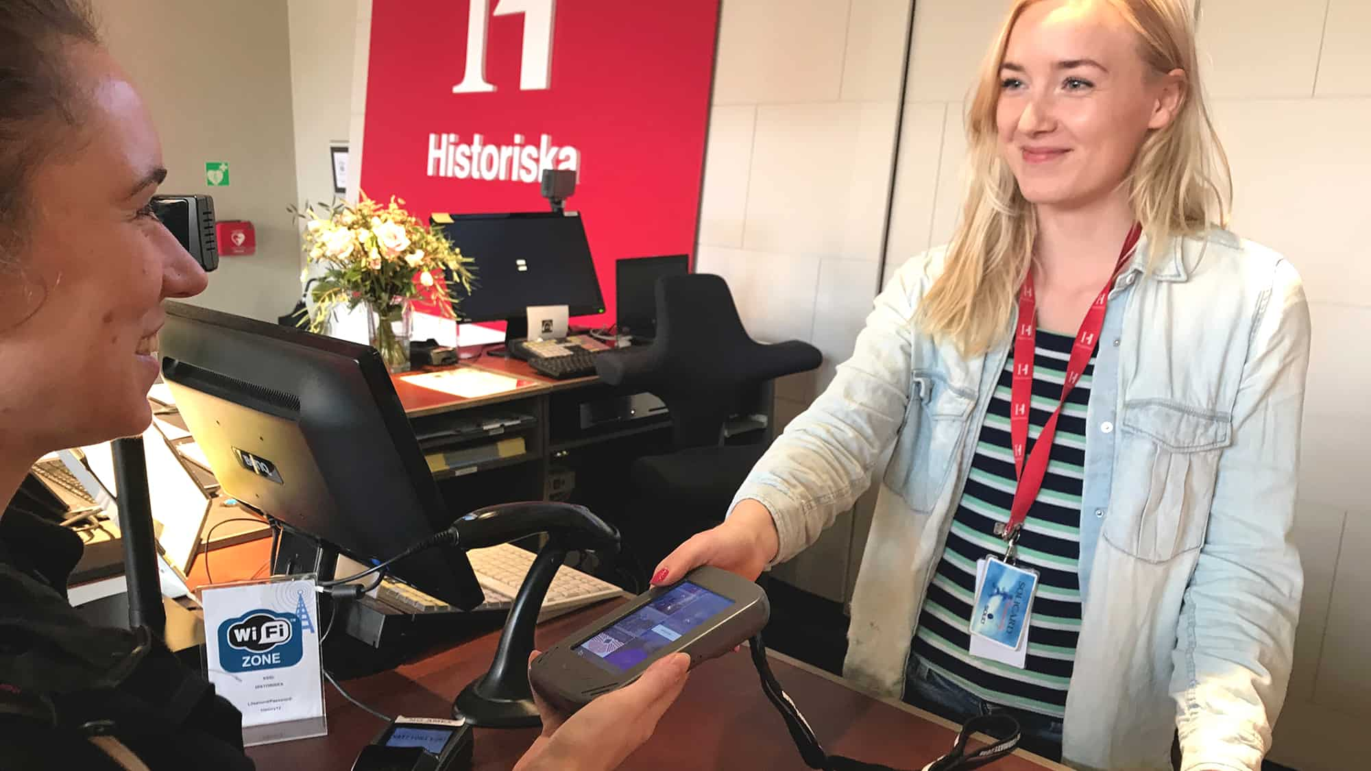 A staff member at Historiska museet is handing over a guide device to a visitor