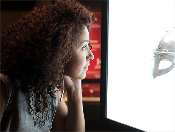Kvinna lyssnar på audioguide på vikingamuseum