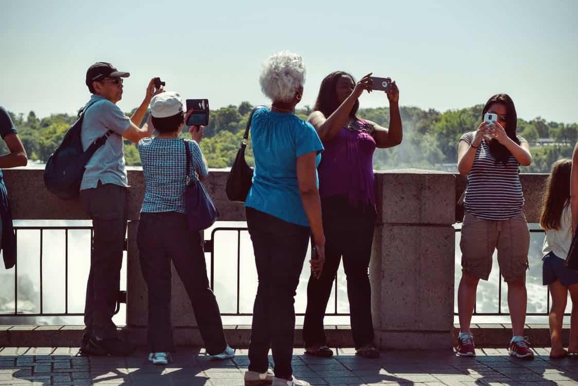 En samling turister tittar på saker i sina mobiler