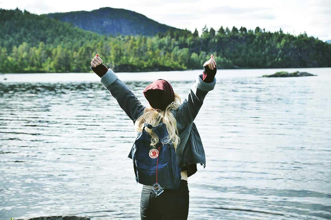 Blond kvinna sträcker nöjt upp armarna framför en skogssjö
